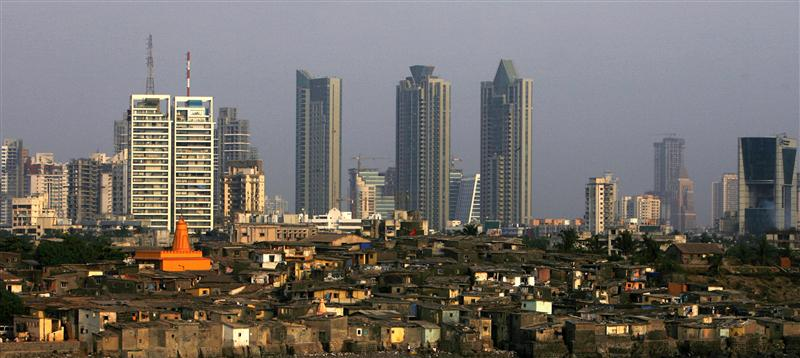 High rise buildings are seen behind a slum in Mumbai
